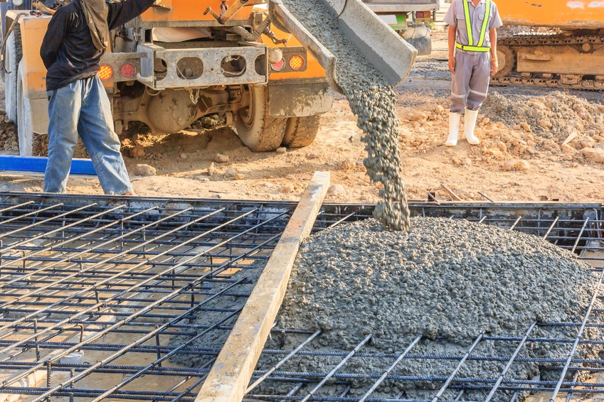 Concrete pouring during commercial concreting floors of buildings in construction site.
